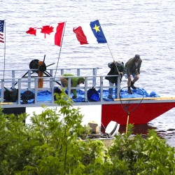 Acadian Queen builders Gerald Soucy and David Wylie plant the Acadian flag on their craft before Thursday's voyage.