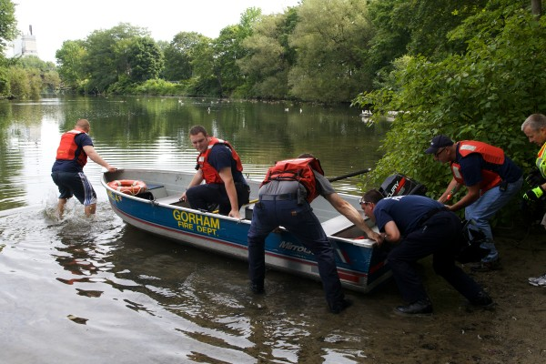 Firefighters and rescue personal launch a boat into the Presumpscot River in Westbrook on Thursday.