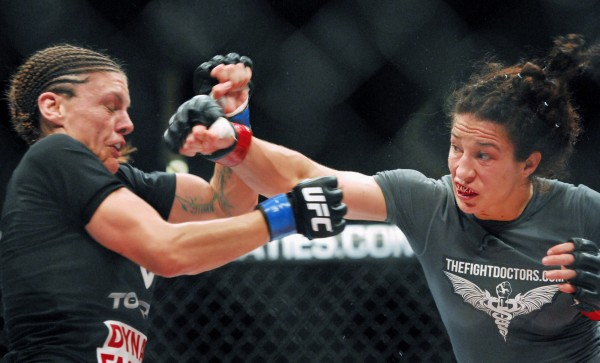 In a women's bantamweight fight, Lauren Murphy (left) tries to block a punch from Sara McMann during the UFC fights at the Cross Insurance Center in Bangor Saturday night. McMann won the fight.