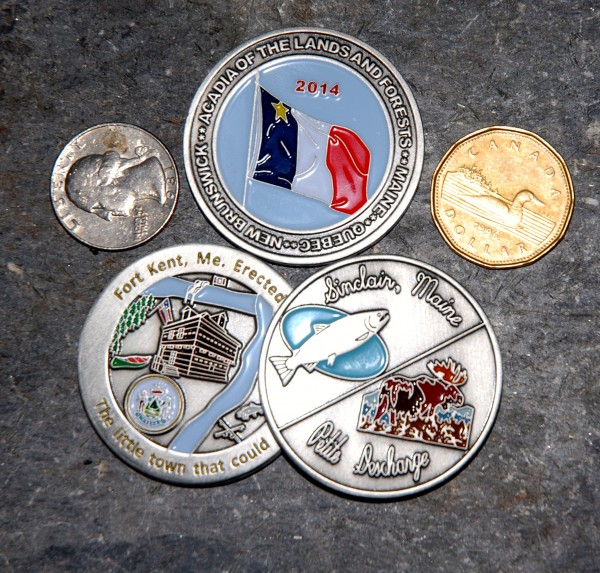 A representative sample of the 2014 World Acadian Congress coins with a US quarter and Canadian dollar for scale.