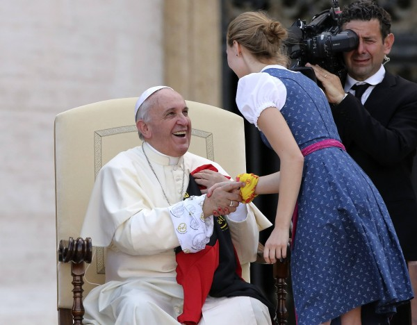 Pope Francis shakes hands with a girl during meeting with altar workers in St Peter's square at the Vatican August 5, 2014. Tens of thousands of altar servers from Germany, Austria gather at the Vatican to meet with Pope Francis.