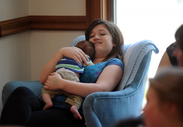 Gabby Nickerson-Peirpont, a resident at the Shepherd's Godparent Home in Bangor, snuggles her 1-month-old son Emery Rafferty.