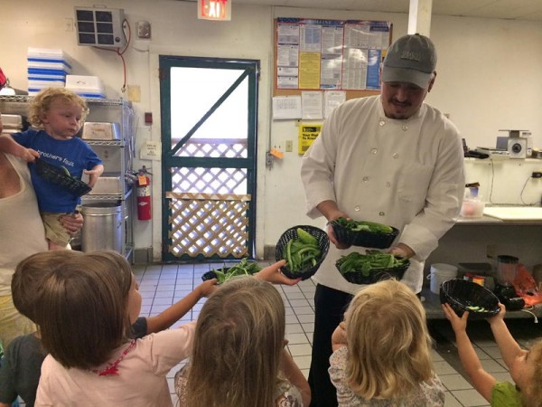 Freeport Grill chef Josh Hambrick accepts the freshly picked vegetables from the Farm to Table Kids children so they can learn about the process of food going from the farm to the table.