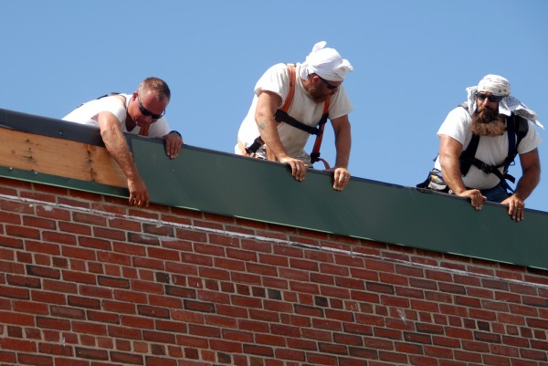 Workers secure insulation as part of a $2.4 million roof replacement at Schenck High School in East Millinocket on Tuesday, Aug. 19, 2014.