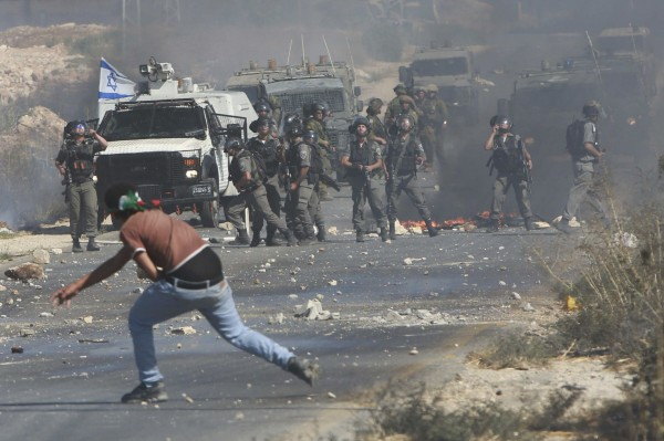 A Palestinian protester throws stones toward Israeli troops during clashes following a demonstration against the Israeli offensive on Friday in Gaza, at the Beit Fourik checkpoint near the West Bank of Nablus.
