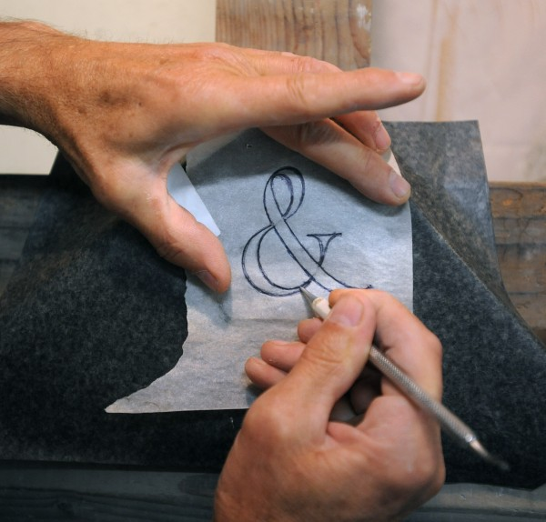 Douglas Coffin demonstrates how a letter or character is traced onto the stone before it is cut by hand at his shop in Belfast.