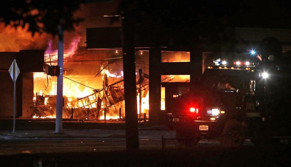 A QuikTrip convenience store burns during a night of rioting in Ferguson, Missouri August 10, 2014. Police arrested 32 people after rioting and looting erupted in Ferguson, Missouri, late on Sunday and spread to neighboring towns in protests that turned violent over the killing of a black teenager by a police officer, officials said on Monday.