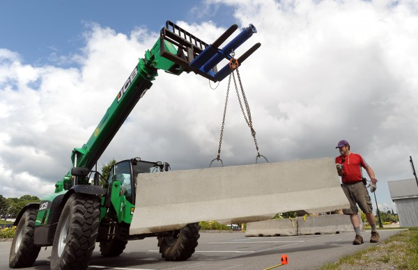 Richard Derbyshire guides a concrete barrier into place as preparation for the 2014 American Folk Festival started at the Bangor Waterfront on Monday.