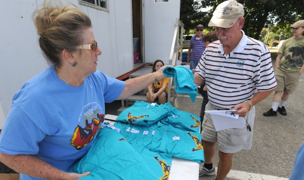 Judy Ingersoll hands a T-shirt to fellow volunteer Phil Newbury while people started signing up to help out during the 2014 American Folk Festival in Bangor.