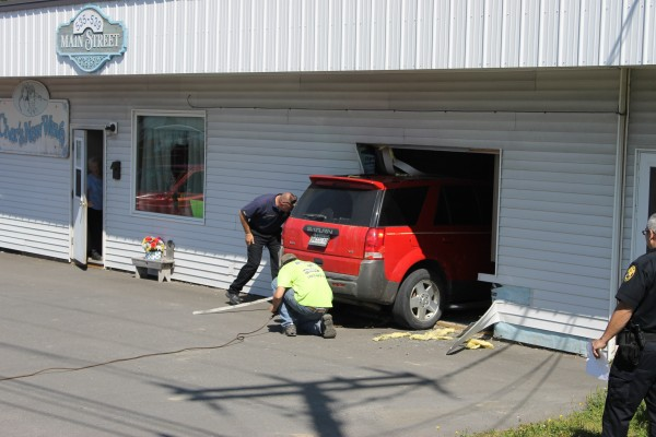 Caribou Fire Chief Scott Susi (left) and Sam Robertson work to extract a 2005 Saturn sport utility vehicle from a Main Street building in Caribou on Friday afternoon.
