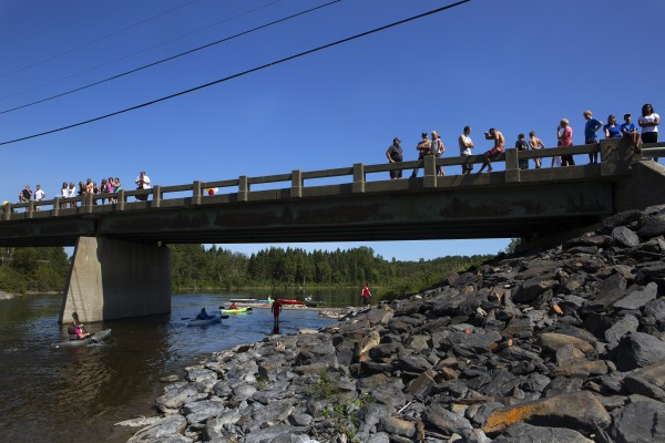 Onlookers watch as kayakers and canoers cross the finish line for the Saucier family reunion in Wallagrass on Sunday as part of the 2014 World Acadian Congress.