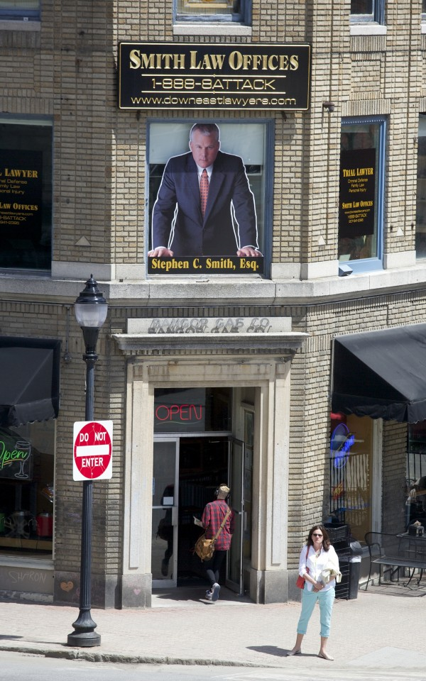 A poster advertising Smith Law Offices hangs above Giacamo's in downtown Bangor.