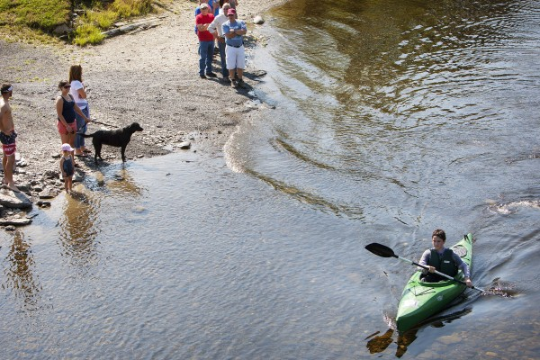 Onlookers cheer for a kayaker traveling to the Saucier family reunion in Wallagrass on Sunday as part of the 2014 World Acadian Congress.