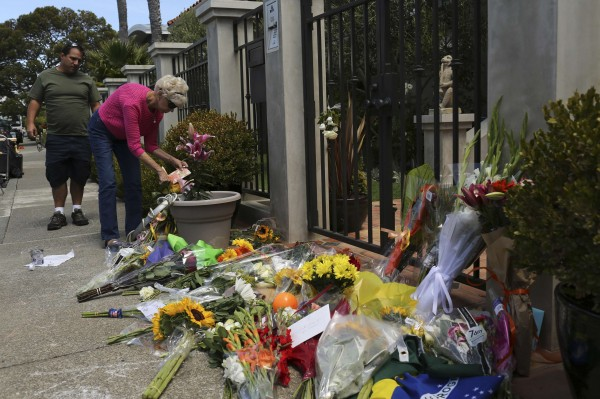 A woman places flowers and a card outside the home of actor Robin Williams in Tiburon, California, on Tuesday. Oscar-winning actor and renowned comedian Williams hanged himself in his California home and died by asphyxia, a coroner said on Tuesday based on preliminary findings.