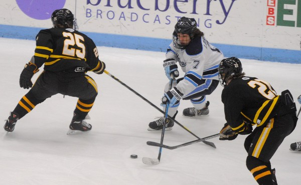 The University of Maine forward Ryan Lomberg (center) battles for the puck with American International's Carson Grolla (left) and David Norris during the first period of a game on Dec. 13, 2013, in Orono.