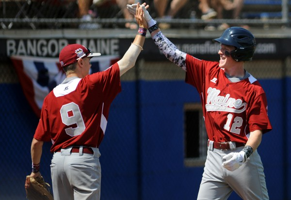 Maine's Dennis Farnham (12) gets a high five from teammate Joey Moir after bringing in a run in the sixth inning of their Senior League World Series game against Canada on Aug. 10. Maine District 3 won 7-2.