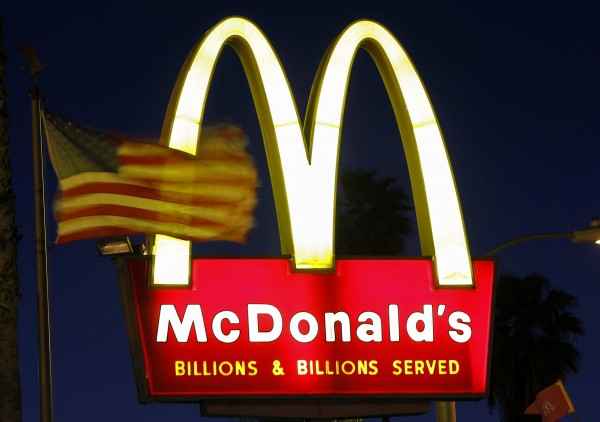 A U.S. flag flutters in the wind in front of a sign for a McDonald's restaurant in Los Angeles in this April 4, 2011 file photo. Through bursting bubbles and crashing markets, revenue and profit at America's top companies have expanded smartly over the past 18 years -- nearly tripling in the case of operating income. A Reuters analysis of revenue, operating profit and head count growth at the 100 largest non-bank companies between 1995 and 2013 documents a steady divergence between their ability to generate earnings and the need to hire employees.