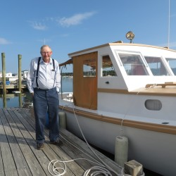 "Ralph Stanley stands beside the boat he built for his father in 1960, ""Seven Girls,"" named for Ralph's seven sisters."
