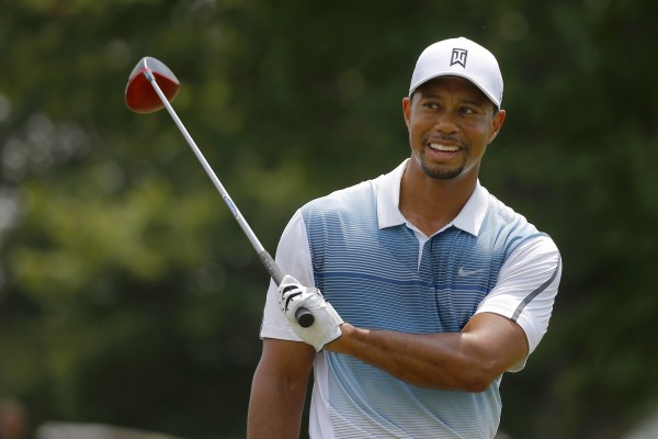 Tiger Woods of the United States smiles while warming up on the practice range at the 2014 PGA Championship at Valhalla Golf Course in Louisville, Kentucky.