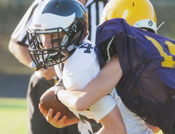 Houlton High School's Garrett Ring (34) is tacked at the sideline by a Bucksport High School player during a scrimmage at Carmichael Field in Bucksport Monday.