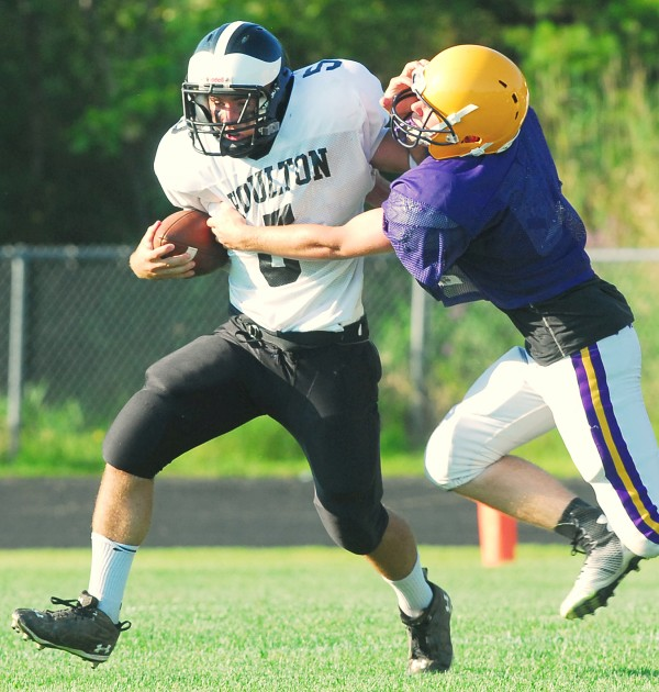 Houlton High School quarterback Jake Drew (5) tries to break free from Bucksport High School's Alex Dyer during a scrimmage Monday at Carmichael Field in Bucksport.