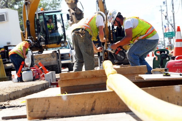 Lance Dionne (right) and Tim Williams of Sullivan and Merritt Constructors work to install a low-pressure natural gas pipeline on West Broadway in Lincoln on Wednesday, Aug. 20, 1014.