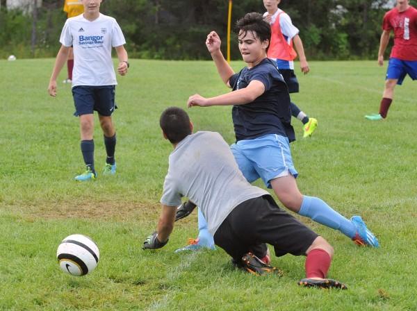 Bangor High School's Sam Putnam (right) gets the ball past goalie Lucas Potts during practice on Monday in Bangor.