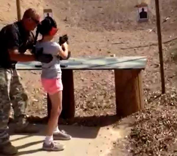 Shooting instructor Charles Vacca stands next to a 9-year-old girl at the Last Stop shooting range in White Hills, Arizona near the Nevada border, on Aug. 25, in this still image taken from video courtesy of the Mohave County Sheriff's Office. The girl accidentally shot and killed her shooting instructor with an Israeli-made Uzi submachine gun when the weapon's strong recoil caused her to lose control of her aim, police said on Tuesday.
