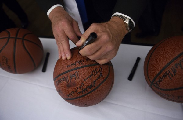 Inaugural class of the Maine Basketball Hall of Fame inductee Dick Whitmore signs basketballs before the induction ceremony Thursday at the Cross Insurance Center in Bangor.