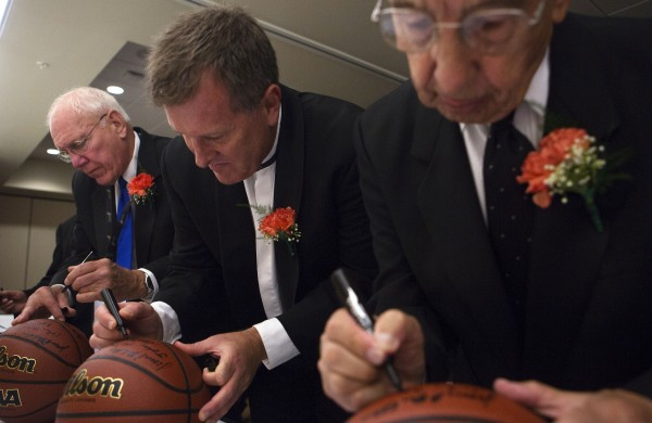Inaugural class of the Maine Basketball Hall of Fame inductees (from left) Dick Whitmore, Matt Hancock and John Mitchell sign basketballs before the induction ceremony Thursday at the Cross Insurance Center in Bangor.