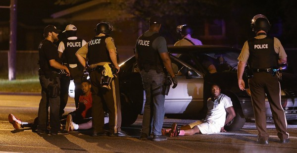 Police search the vehicle of three men they believed may have been involved in an assault on a man with a dog near the Quik Trip on Wednesday, Aug. 13, 2014, in Ferguson, Missouri. Two of the vehicle's occupants were arrested and one was released.