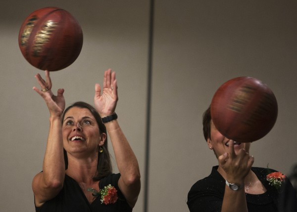 Inaugural class of the Maine Basketball Hall of Fame inductees Joanne Palombo-McCallie (left) and Rachel Bouchard spin basketballs on their fingers before the induction ceremony Thursday at the Cross Insurance Center in Bangor.