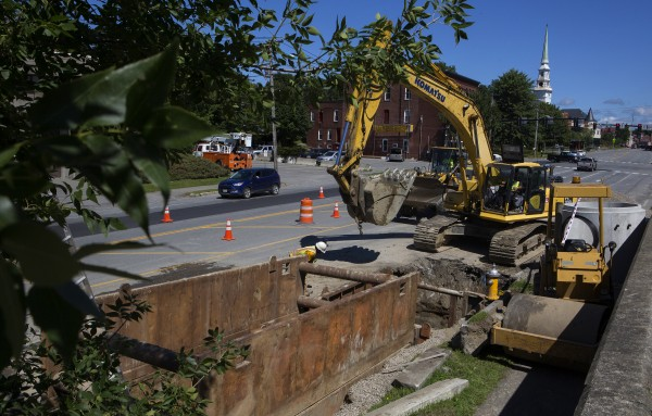 Construction crews work to dig out dirt near the intersection of Main Street and Cedar Street in Bangor on Tuesday.