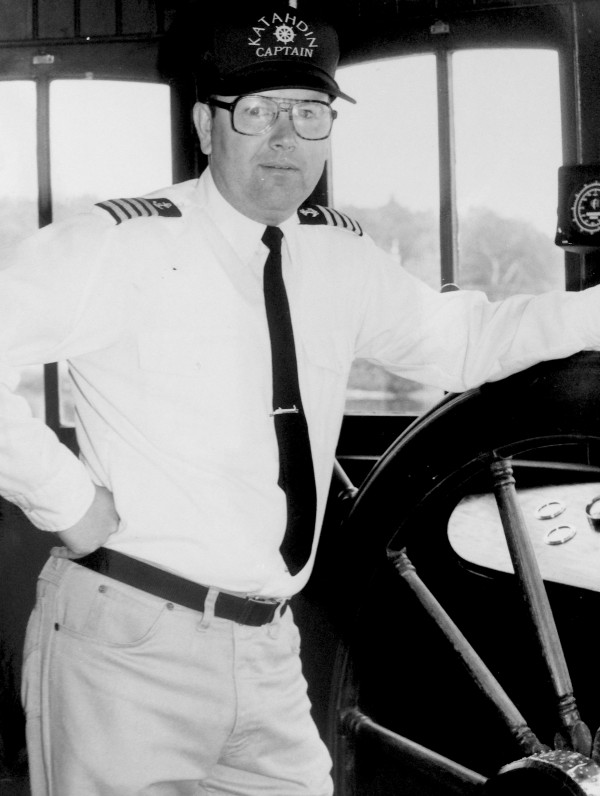 A Katahdin ferry captain stands at the helm of the ship in Greenville, Maine.