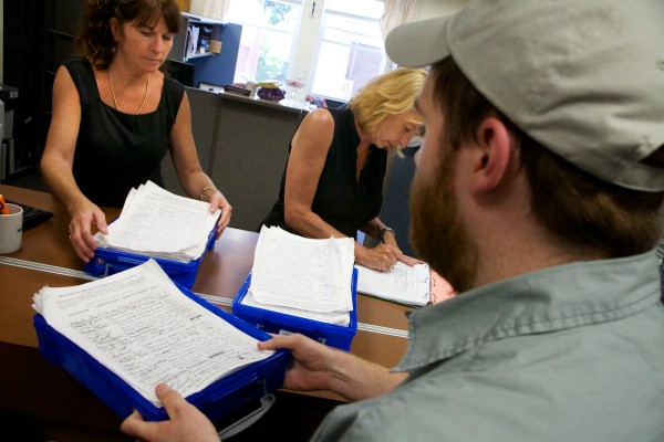 Assistant city clerks Alice Kelley (left) and Karen Morrill accept petitions as marijuana advocates turn in 1,521 signatures seeking a legalization referendum at City Hall in South Portland in July.