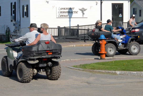 ATV riders turn onto Penobscot Avenue after having ice cream cones in a nearby park in Millinocket in 2012.
