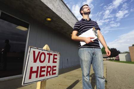 Nick Murray, a volunteer with the Marijuana Policy Project, waits outside the York polls at York High School in hopes of collecting signatures from voters on June 10.