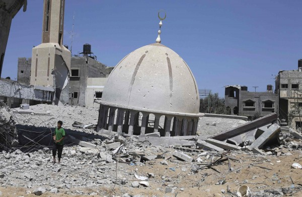 A Palestinian boy stands next to the remains of a mosque in Khuzaa town, which witnesses said was heavily hit by Israeli shelling and air strikes during Israeli offensive, in the east of Khan Younis in the southern Gaza Strip on Wednesday.