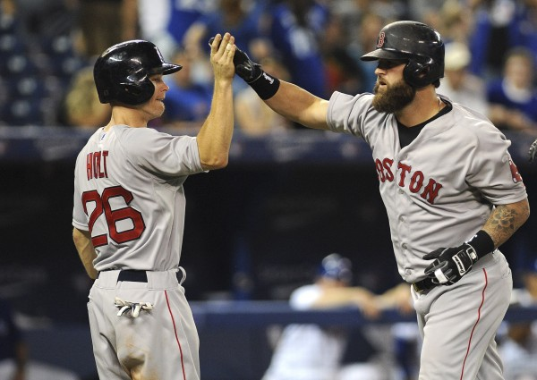 Boston Red Sox designated hitter Mike Napoli (right) is congratulated by shortstop Brock Holt after hitting a three-run home run in the 11th inning against the Toronto Blue Jays at Rogers Centre in Toronto Tuesday night.