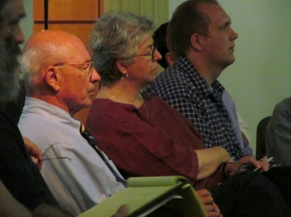 Portland Mayor Michael Brennan and Anna Eleanor Roosevelt, head of Goodwill Industries of Northern New England, listen Wednesday night as members of the public weigh in on a proposal to raise the minimum wage in Maine's largest city.
