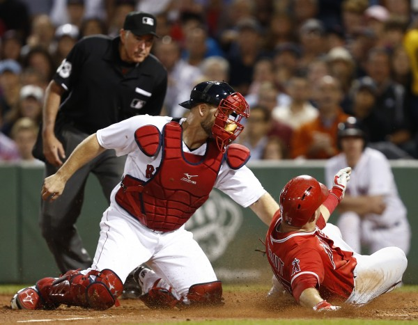 Los Angeles Angels center fielder Mike Trout (right) slides into home plate as Boston Red Sox catcher David Ross (left) applies a tag during the fifth inning at Fenway Park.