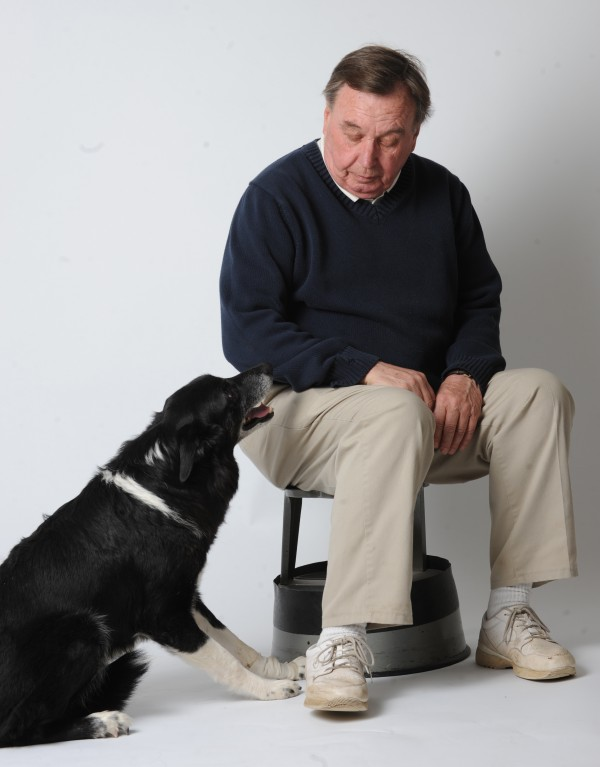 Mickey, a rescued border collie, sits with his master, Tom Duffy, during an interview.
