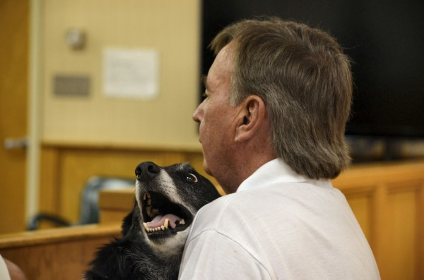 Tom Duffy holds his border collie, Mickey, in his arms in Newport District Court.