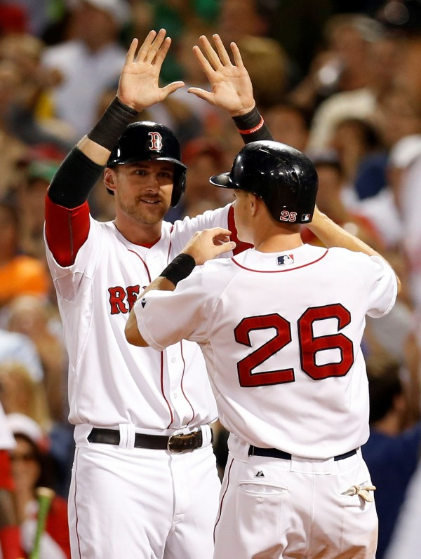 Boston's Will Middlebrooks (left) welcomes shortstop Brock Holt (26) to home plate after scoring during the sixth inning against the Houston Astros at Fenway Park in Boston Thursday night.