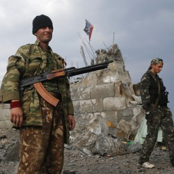 Pro-Russian separatists walk at a destroyed war memorial on Savur-Mohyla, a hill east of the city of Donetsk, Aug. 28, 2014.