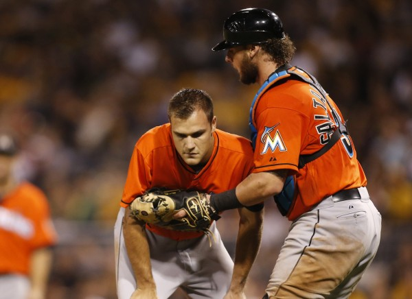 Miami Marlins relief pitcher Dan Jennings (left) is assisted by catcher Jarrod Saltalamacchia after Jennings was hit in the head by a line drive off the bat of Pittsburgh's Jordy Mercer during the seventh inning of Thursday night's game at PNC Park. Jennings is expected to miss at least a week with a concussion.
