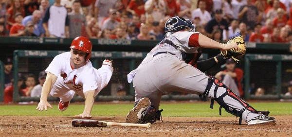 The St. Louis Cardinals' Shane Robinson (left) scores past Boston Red Sox catcher Christian Vazquez in seventh-inning action on Tuesday, Aug. 5, 2014, at Busch Stadium in St. Louis.