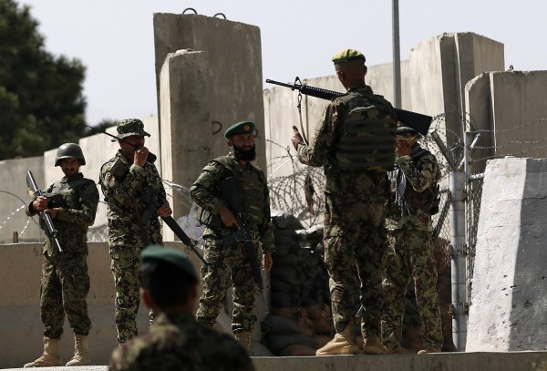 Afghan National Army soldiers keep watch at the gate of a British-run military training academy Camp Qargha, in Kabul August 5, 2014. One serviceman was killed and 14 wounded when a man in Afghan army uniform opened fire on international and Afghan forces at a military training academy in Kabul on Tuesday, the German military and Afghan officials said.