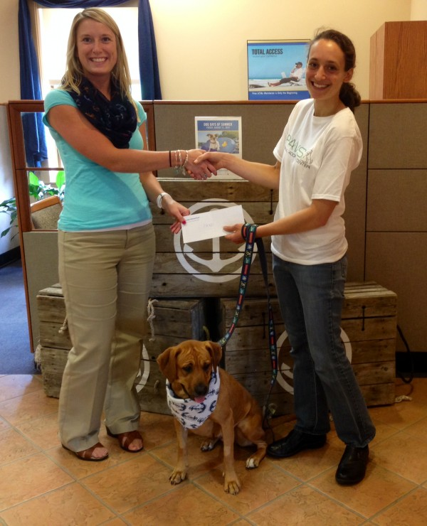 Camden National Bank Assistant Branch Manager Heather Burns presents a donation to Mabel and P.A.W.S. Director of Development/Volunteer Coordinator, Joelle Albury.
