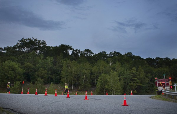 Emergency officials set up cones after a two-car accident killed three people on Tuesday in Dedham.